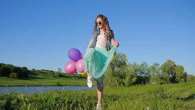 Happy girl teenager with color strand of hair in hair and balloons in hands having fun on green meadow near lake. Happy girl adolescent with color strand of hair stock video footage