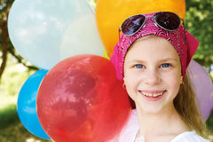 Happy girl is in a amusement park with colorful balloons. Stock Photography