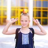 Little Girl Smiling With Apple On Her Head. stock image