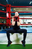 Happy girl athlete sits on a boxing ring. beautiful woman smiling and holding hands in boxing gloves near the face. stock image