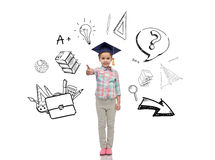 Happy girl in bachelor hat showing thumbs up. Childhood, school, education, learning and people concept - happy girl with in bachelor hat or mortarboard showing Royalty Free Stock Photography