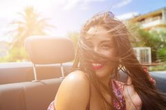 Happy girl in the back seat of convertible car. Happy brunette girl sitting and smiling in the back seat of convertible car. Sun effect applied stock photography