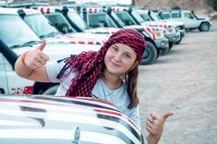 Happy girl on the background of the group of SUVs royalty free stock photos