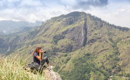 Happy girl with a backpack tourist photographer to take pictures on the camera in the mountains and enjoy the view and nature royalty free stock photos