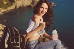 Happy girl backpacker is sitting on rock over sea view Royalty Free Stock Images