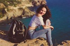 Happy girl backpacker is sitting on rock peak over sea Stock Image