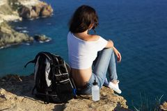Happy girl backpacker is sitting on rock peak over sea Stock Photography