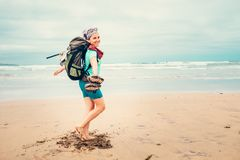 Happy girl backpacker traveler runs barefoot on the sand ocean b. Each Stock Photography