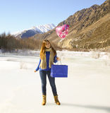 Happy girl with a balloon and a package with a gift Stock Images