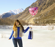Happy girl with a balloon and a package with a gift Royalty Free Stock Photo
