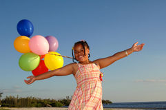 Happy girl with balloons. A smiling girl with balloons outdoors and arms stretched out Royalty Free Stock Images
