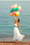 Happy girl with balloons. Girl with balloons in a skirt on the beach Stock Images
