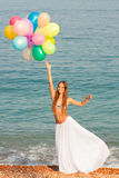Happy girl with balloons. Girl with balloons in a skirt on the beach Royalty Free Stock Images