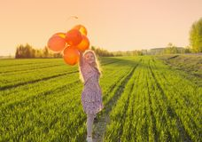 Happy girl with balloons on field Royalty Free Stock Photos