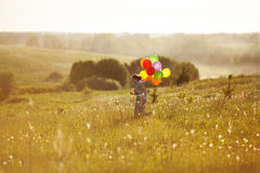 Happy girl with balloons running on the field Royalty Free Stock Images