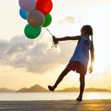 Happy girl with balloons at sunset Royalty Free Stock Photo