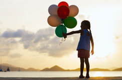 Happy girl with balloons at sunset Royalty Free Stock Photography