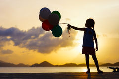 Happy girl with balloons at sunset Stock Photography