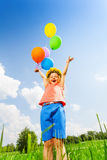 Happy girl with balloons wearing flower circlet. Standing in the park Royalty Free Stock Images