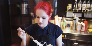 Happy girl Barista gives coffee  to the customers Stock Photo