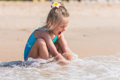 Happy girl in a bathing suit on the beach on a sunny day Stock Photos
