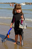 Happy girl on beach with colorful face masks and snorkels, sea i Royalty Free Stock Image