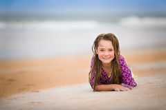 Happy girl at the beach. Girl in rash guard swimsuit with wet hair laying on the beach stock photography
