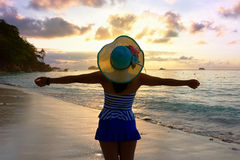 Happy girl on the beach at sunrise. Tourist girl in a swimsuit blue and white striped hat standing on beach with pleasure the beautiful landscape of sky and sea Royalty Free Stock Photo