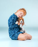 The happy girl and a beagle puppie on gray background. The happy girl and beagle puppie on gray background Royalty Free Stock Photo