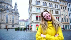 Happy girl in beautiful European city Dresden sends greetings, standing in center of square against background of stock footage