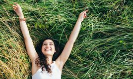 Happy girl in a bed of grass stock image