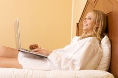 Happy Girl in Bed Using a Laptop Computer Royalty Free Stock Photos