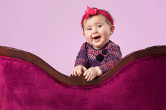 Happy girl behind sofa. Portrait of a smiling toddler girl behind a curved childs sofa Royalty Free Stock Images