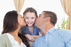 Happy girl being kissed by parents Royalty Free Stock Image