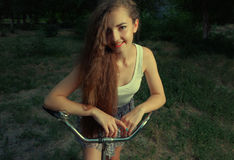 Happy girl on bicycle smiling in countryside looking at camera Royalty Free Stock Photography