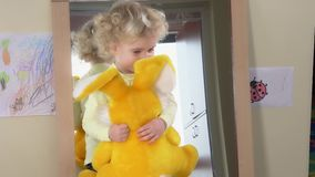Happy girl with big plush rabbit pose in front of mirror at home stock footage