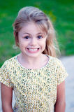 Happy young girl. Portrait of a happy girl outdoors with grass in the background Royalty Free Stock Photos