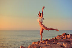 Happy girl in bikini jumping on a beach at sunset or sunrise Stock Photography