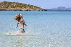 Happy girl in bikini running seawater. Happy smiling girl in a blue bikini running on sea water with their hands raised Royalty Free Stock Image