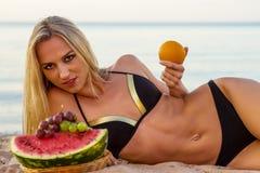Happy girl in black bikini relaxing on the sand Stock Photo