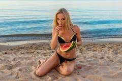 Happy girl in black bikini relaxing on the sand Royalty Free Stock Photo