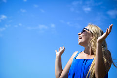 Happy girl in black sunglasses on bright blue sky Stock Images