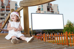 Happy girl and blank board. Smiling girl in playground  with blank advertising panel in background Royalty Free Stock Images