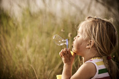 Happy girl blowing bubbles outdoors Royalty Free Stock Image