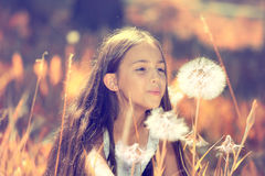 Happy girl blowing dandelion flower. Outdoor closeup portrait of a beautiful, happy young Girl Blowing Dandelion flower on a sunny summer day. Life Leisure royalty free stock photos