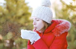 Happy girl blowing the snow on hands outdoors in winter Stock Photography