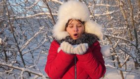 Happy girl blowing snowflakes at sunset and smiling in winter park. young girl blows snowflakes from her hands, in. Winter forest. child plays in winter in the stock footage