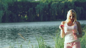 Happy girl blowing soap bubbles in summer park near the lake. Slowly.  stock footage