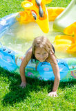 Happy girl in blowup pool Royalty Free Stock Photography
