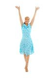 Happy girl in blue dress with hands up Stock Image